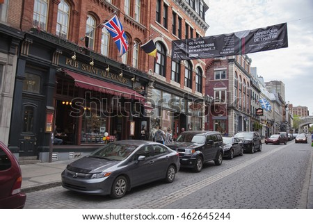 QUEBEC CITY - MAY 25, 2016: Rue St. Jean in old Quebec City is lined with quaint shops and restaurants which draw millions of tourists each year.