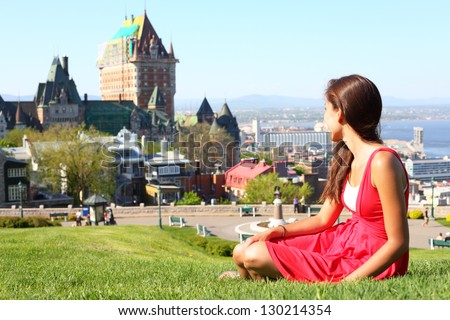 Quebec City scape with Chateau Frontenac and young woman in red summer dress sitting in grass enjoying the view. Tourist or student in Quebec City, Quebec, Canada. - stock photo