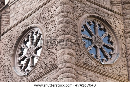 Queen's Park Building. Vintage round windows on tower. Romanesque Revival Architecture. Old fashioned vintage circular windows with textured sculpted details on tower walls, in Toronto, Canada.