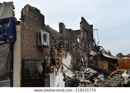 QUEENS, NY - NOVEMBER 11: People working on buildings ruins ater massive fire in the Rockaway due to impact from Hurricane Sandy in Queens, New York, U.S., on Novemeber 11, 2012. - stock photo