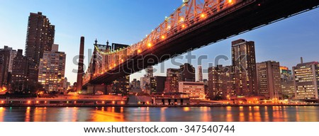 Queensboro Bridge over New York City East River at sunset with river reflections and midtown Manhattan skyline illuminated.
