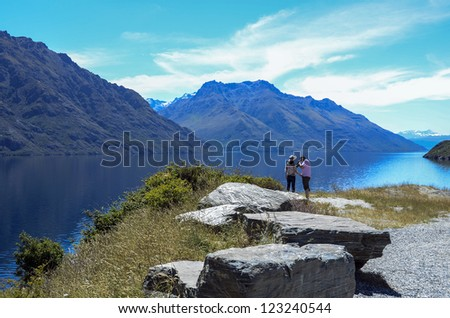 QUEENSTOWN, NEW ZEALAND - DECEMBER 24: Tourists enjoy mountain views overlooking Lake Wakatipu near Queenstonw on December 24, 2012 in Queenstown, New Zealand. Queenstown is a popular alpine resort. - stock photo