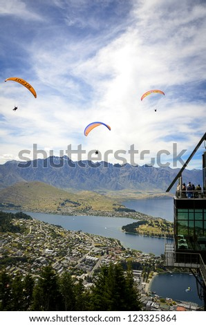 QUEENSTOWN, NEW ZEALAND - DECEMBER 24: Tourists on an alpine observation deck watch passing paragliders on December 24, 2012 in Queenstown, New Zealand. Queenstown is a popular summer resort. - stock photo
