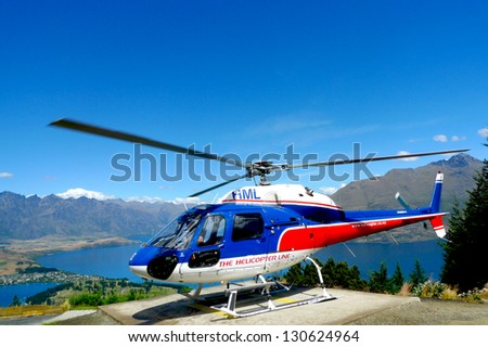 QUEENSTOWN, NEW ZEALAND - JANUARY 26: Helicopter on top of  Bob's Peak with the view on Lake Wakatipu in Queenstown, New Zealand on January 26, 2009. Queenstown is the 'Adventure Capital of the World' - stock photo