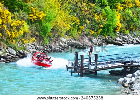 QUEENSTOWN, NEW ZEALAND -  November 18: Tourists enjoy a high-speed boat ride on Queenstown's Shotover river on November 18, 2014 in Queenstown, New Zealand. Queenstown is a popular alpine resort - stock photo