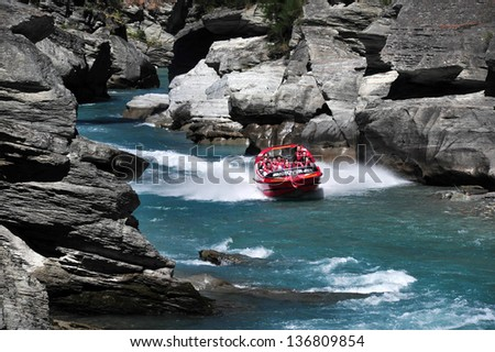 QUEENSTOWN,NZ - FEB 20: Tourists enjoy a high speed jet boat ride on the Shotover River on February 20, 2009 in Queenstown, New Zealand. Queenstown is one of the most popular summer resort in NZ. - stock photo