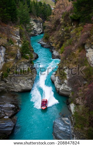 QUEENSTOWN,NZ - JULY 24: Tourists enjoying a high speed jet boat ride on the Shotover River on July 24, 2014 in Queenstown, New Zealand. Queenstown is a popular spot to spend the winter in NZ. - stock photo