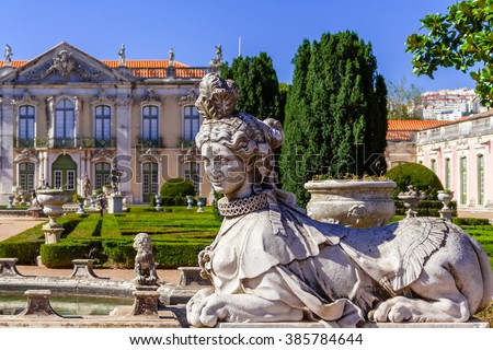 Queluz, Portugal. Sphinx sculpture at the Neptune gardens and Cerimonial Facade on the Queluz Royal Palace. Formerly used as the Summer residence by the Portuguese royal family. - stock photo