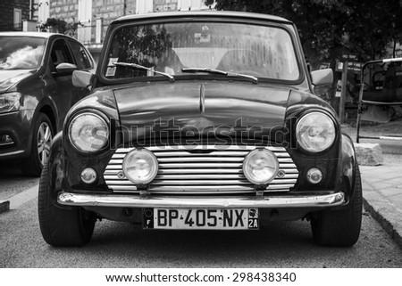 Quenza, France - July 1, 2015: Black Mini cooper car stands parked, close-up photo, front view - stock photo