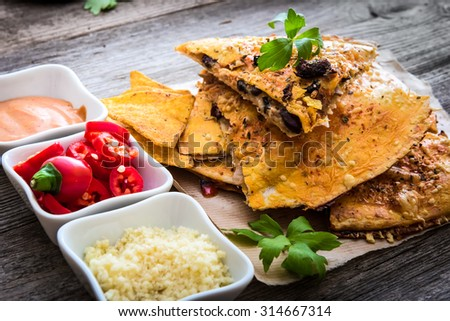 quesadilla on parchment with sause and spices on a wooden background - stock photo