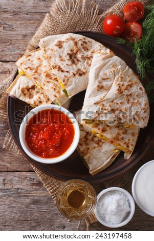 Quesadilla sliced with vegetables and sauce on a plate close-up. vertical top view