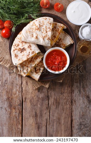 Quesadilla sliced with vegetables and sauce on a plate. vertical top view  - stock photo