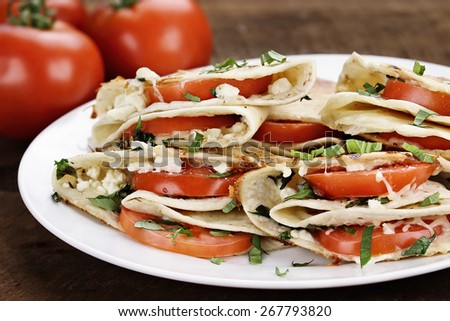Quesadillas vegetarian wraps made with goat cheese or feta, tomatoes, mozzarella and fresh herbs, Extreme shallow depth of field. - stock photo