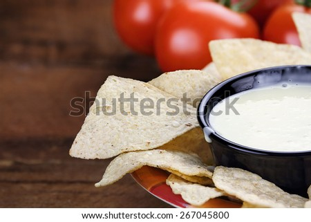 Queso Blanco or White Cheese Sauce with corn tortilla chips and fresh tomatoes. Extreme shallow depth of field with selective focus on cheese dip. - stock photo
