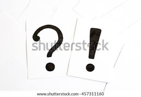 Question and exclamation mark on the paper a few pieces of paper on a white background - stock photo
