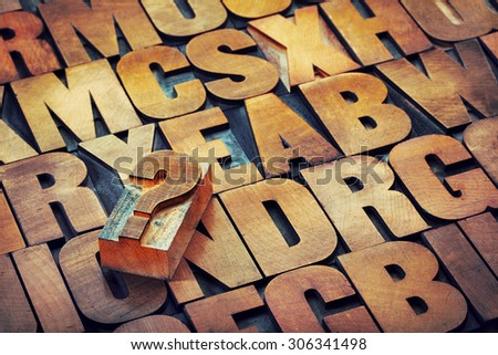 question mark and alphabet in vintage letterpress wood type printing blocks stained by color inks - stock photo