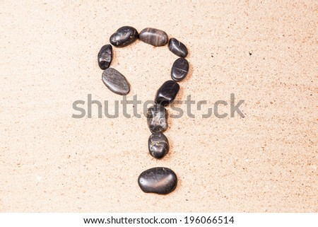 question mark drawn with pebbles on the sand of a beach