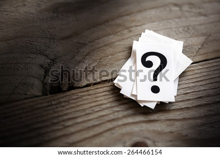 Question mark heap on table concept for confusion, question or solution - stock photo