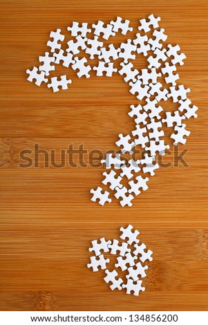 question mark made by puzzle on wood background - stock photo