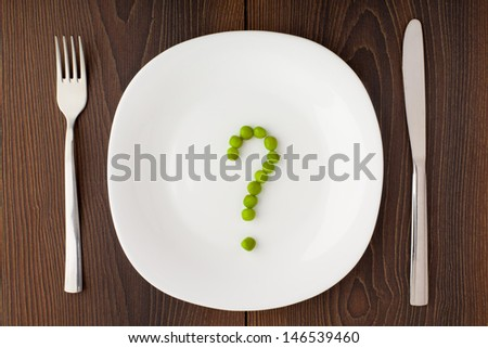Question mark made of peas on plate - stock photo