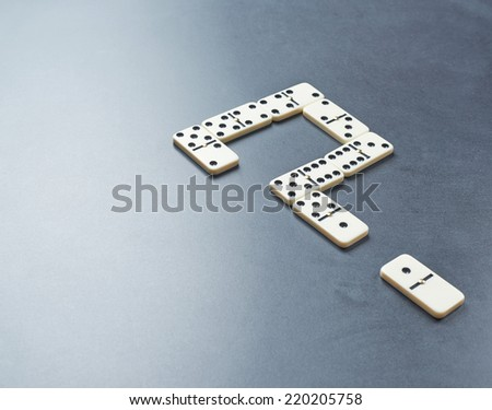 Question mark made with the white domino bones over the dark gray surface as a copyspace background composition - stock photo