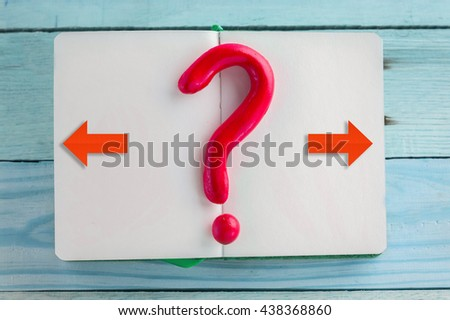question mark object with open page notebook  on wooden table :Concept for confusion - stock photo