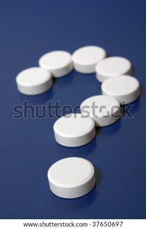 Question mark of white tablets on dark blue background. - stock photo