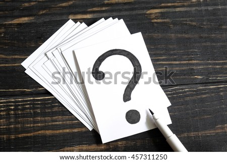 Question mark on the paper, a pencil brush and a few pieces of paper on a wooden table - stock photo