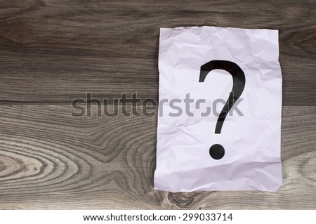 question marks on paper on wooden table - stock photo