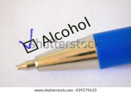 Questionnaire - blue pen and the inscription ALCOHOL with check mark on the white paper