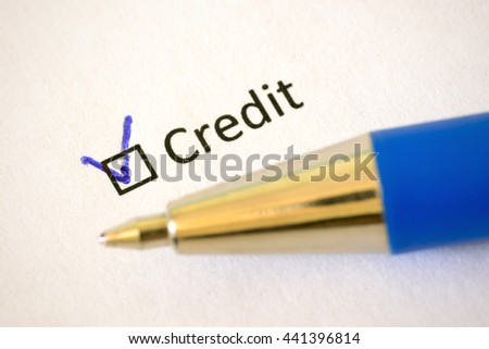 Questionnaire. Blue pen and the inscription CREDIT with check mark on the white paper - stock photo