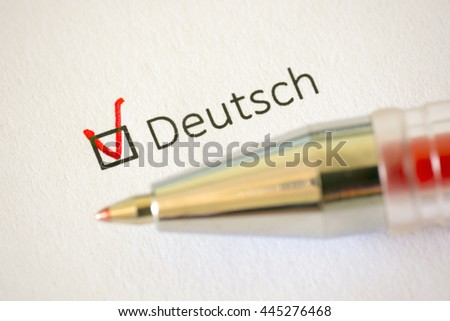 Questionnaire. Red pen and the inscription GERMAN with cross on the white paper