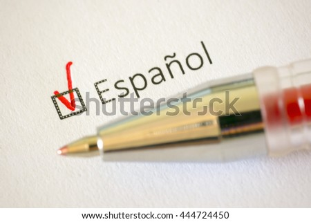 Questionnaire. Red pen and the inscription SPANISH with cross on the white paper
