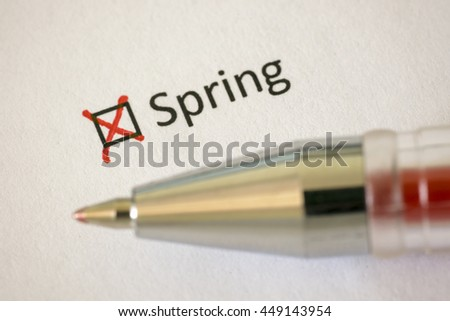 Questionnaire. Red pen and the inscription SPRING with cross on the white paper