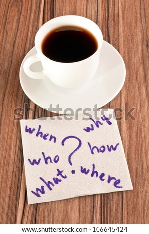 Questions on a napkin and cup of coffee - stock photo
