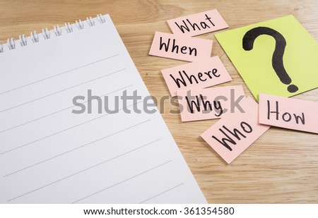 Questions what, when, where, why, who, how and white notebook on wood background - stock photo
