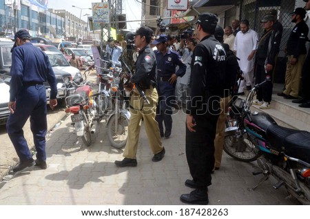 QUETTA, PAKISTAN - APR 15: Security official arresting guards of a private bank after  robbery in a private bank located at Double Road on April 15, 2014 in Quetta.