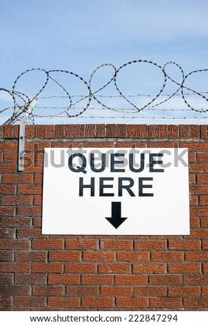 Queue Here Sign On Wall With Razor Wire - stock photo