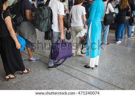 Queue of people in Noi Bai airport, Vietnam. Focus on female staff wearing Vietnamese long dress Ao Dai