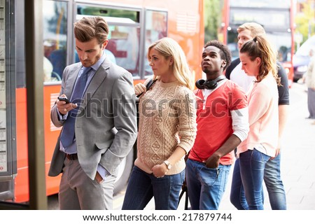 Queue Of People Waiting At Bus Stop - stock photo