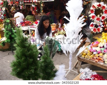 QUEZON CITY, PHILIPPINES - NOVEMBER 22, 2015: A woman sells christmas decors in Dapitan Market. Dapitan Market is well known for its wide variety of home decor products. - stock photo