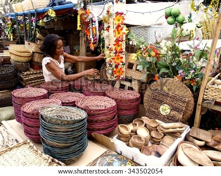 QUEZON CITY, PHILIPPINES - NOVEMBER 22, 2015: A woman sells decorative plants, flowers, christmas decors and baskets in Dapitan Market. This arket is known for its wide variety of home decor products. - stock photo