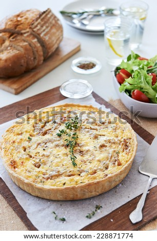 Quiche lorraine tart frittata pie light meal for lunch served with green salad and loaf of bread - stock photo