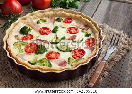 Quiche lorraine traditional homemade french food preparation recipe with bacon, broccoli, cheese and tomatoes in baking dish on vintage wooden table background. Rustic style. - stock photo