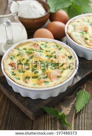 Quiche pie with fish and nettles on the table