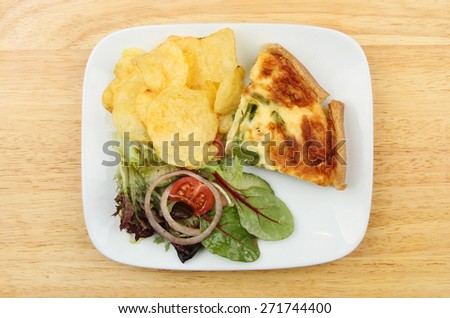 Quiche, salad and potato crisps on a plate on a wooden board - stock photo