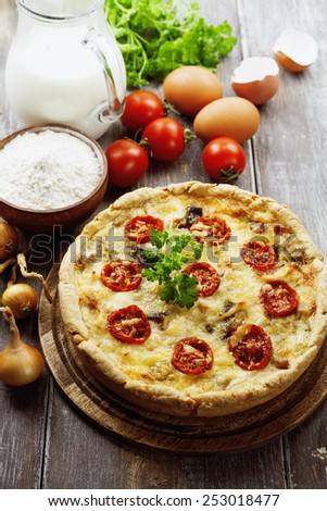 Quiche with chicken, mushrooms and cherry tomatoes on a wooden table