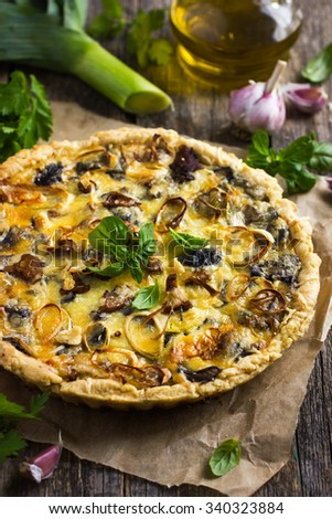 quiche with mushrooms, leek and cheese on rustic background - stock photo