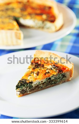Quiche with spinach and rocotta cheese - one portion on a plate, the other part in background - stock photo