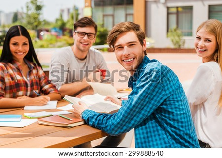 Quick meetin. Group of happy young people looking at camera and smiling while sitting at the wooden desk outdoors - stock photo